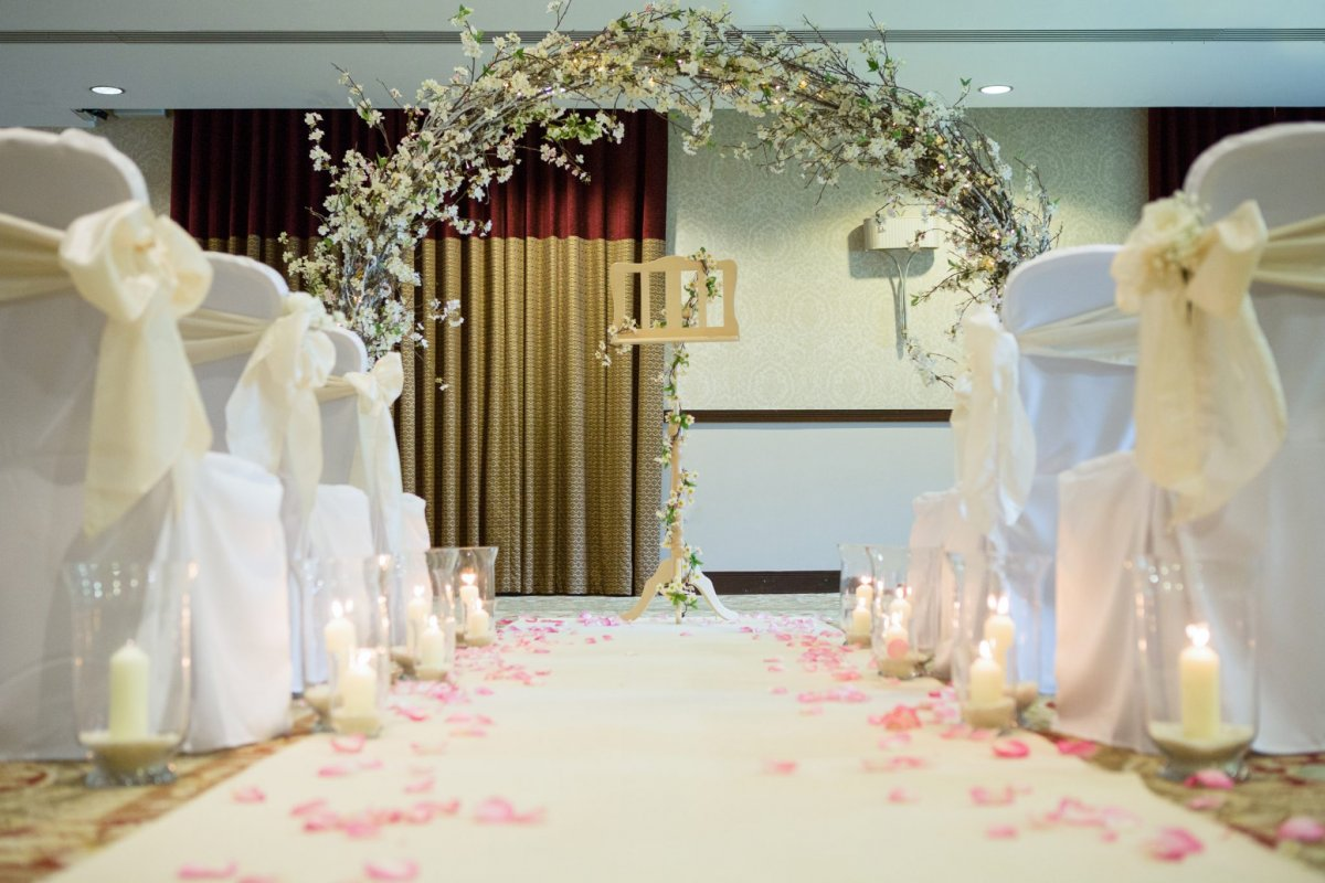 Floral wedding arch & covered white chairs