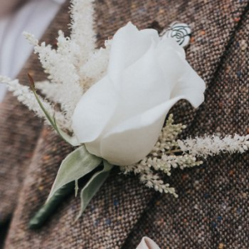 Groomsmen buttonhole of a white rose and astible